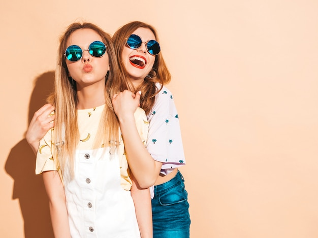 Duas garotas loiras hipster sorrindo lindas jovens em roupas de camiseta colorida na moda verão. e dando air kis Foto gratuita