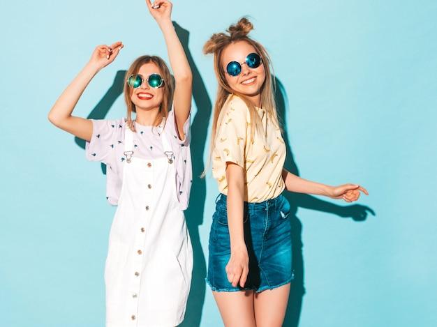 Duas garotas loiras hipster sorrindo lindas jovens em roupas de camiseta colorida na moda verão. Foto gratuita