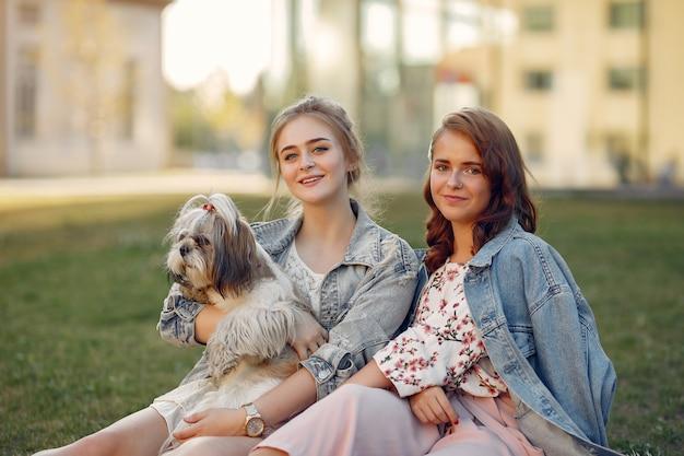 Duas garotas sentado em um parque com um cachorrinho Foto gratuita