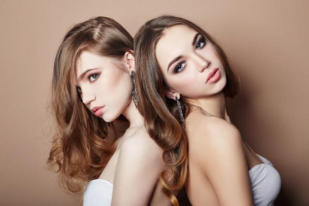 Duas garotas sexy jovens moda loira abraçando a maquiagem Foto Premium