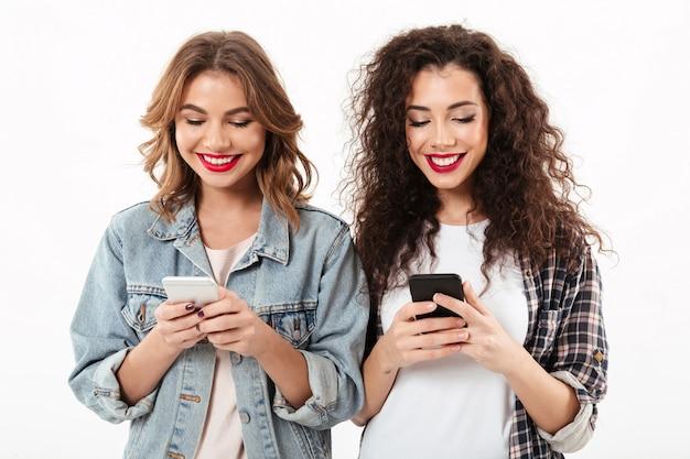 Duas garotas sorridentes, escrevendo a mensagem no smartphone ther sobre parede branca Foto gratuita