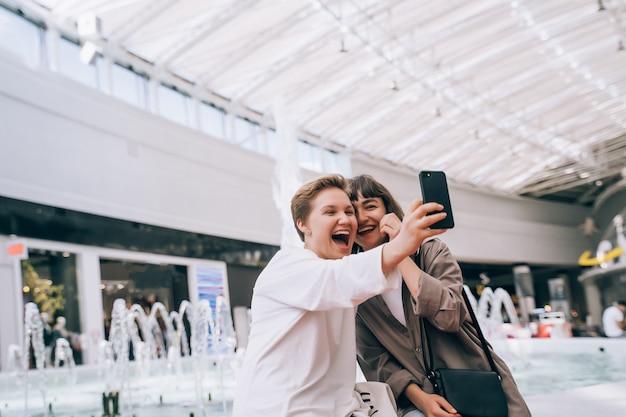 Duas garotas tiram uma selfie no shopping, ao lado de uma fonte Foto gratuita
