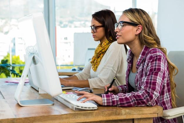 Duas garotas trabalham no escritório no computador e tablet Foto Premium