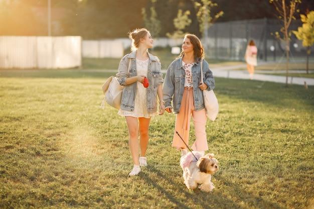 Duas garotas wallking em um parque com um cachorrinho Foto gratuita