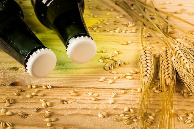 Duas garrafas de cerveja e espigas de trigo no pano de fundo de madeira Foto gratuita