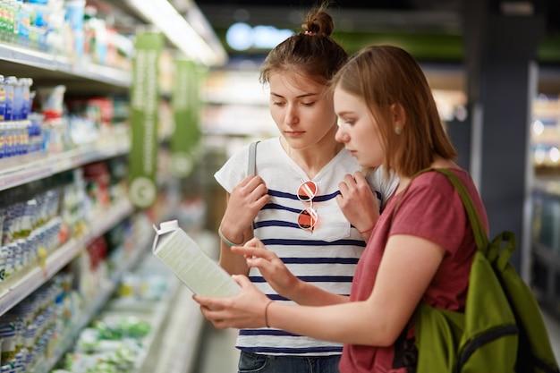 Duas irmãs bonitas do sexo feminino vão às compras juntas, ficam na mercearia, selecionam leite fresco em um recipiente de papel, leem rótulo, carregam mochilas, têm expressões sérias. conceito de pessoas e comércio Foto Premium