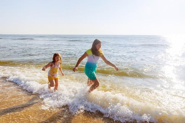 Duas irmãs brincando na praia ao pôr do sol Foto Premium