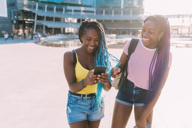 Duas irmãs de mulheres ao ar livre usando telefone inteligente se divertindo Foto Premium