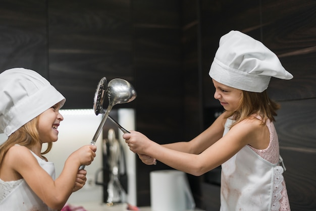Duas irmãs de sorriso bonitos em chapéus do chef estão lutando com utensílio de cozinha Foto gratuita