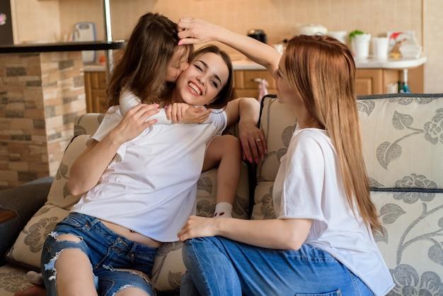 Duas irmãs e filha pequena que sorriem e que abraçam em casa o fundo interior. Foto Premium