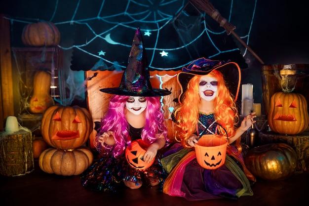 Duas irmãs engraçadas bonitos comemoram o feriado. crianças alegres em fantasias de carnaval prontas para o halloween. Foto Premium