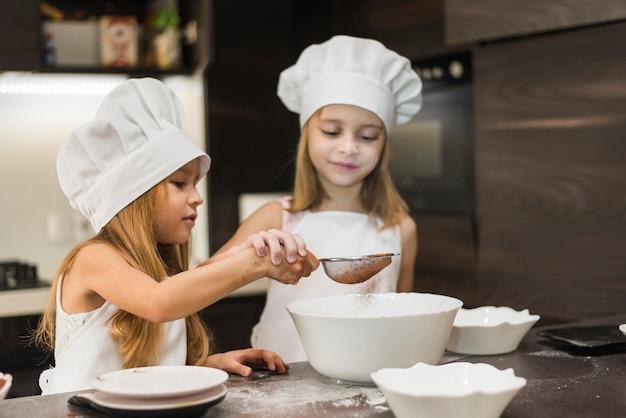 Duas irmãs fofos peneirando o cacau em pó através de filtro na cozinha Foto gratuita