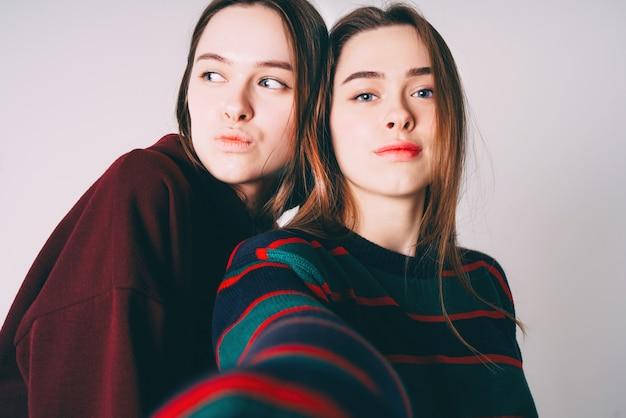 Duas irmãs gêmeas lindas garotas em casual tomando selfie Foto Premium