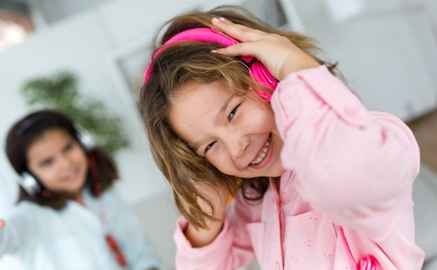Duas irmãs novas que escutam a música e que dançam em casa. Foto gratuita