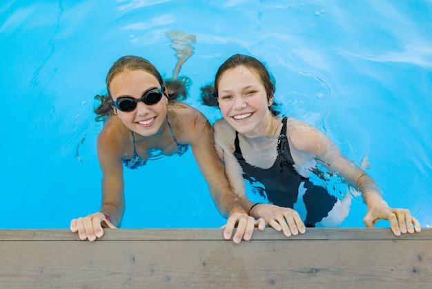 Duas jovens adolescentes se divertindo na piscina. Foto Premium