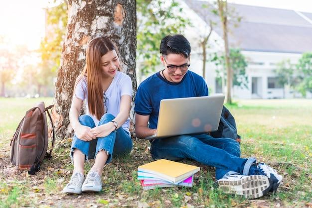 Duas jovens asiáticas que estudam sobre tarefas domésticas e exame final para testes com laptop Foto Premium
