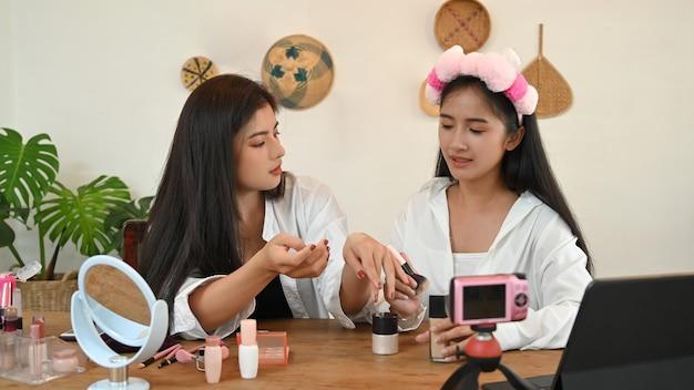 Duas jovens blogueiras de beleza gravando vídeo em casa. Foto Premium