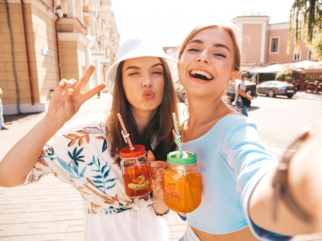 Duas jovens bonitas garotas hipster sorridentes em roupas da moda verão Foto gratuita