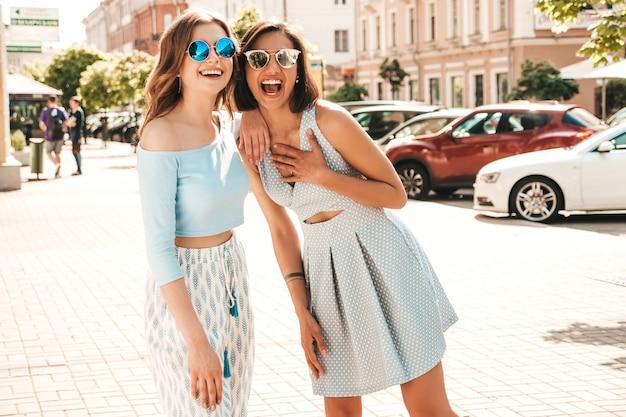Duas jovens bonitas hipster garotas sorridentes em roupas da moda no verão. mulheres despreocupadas sexy posando na rua fundo em óculos de sol. modelos positivos se divertindo e abraçando Foto gratuita