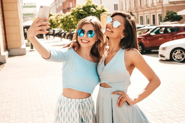 Duas jovens bonitas hipster garotas sorridentes em roupas da moda no verão. mulheres despreocupadas sexy posando no fundo da rua em óculos de sol. eles tirando fotos de auto-retrato de selfie no smartphone ao pôr do sol Foto gratuita