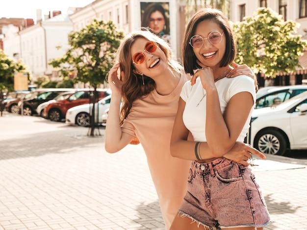 Duas jovens bonitas hipster garotas sorridentes em roupas da moda no verão. mulheres despreocupadas sexy posando no fundo da rua em óculos de sol. modelos positivos se divertindo e enlouquecendo Foto gratuita