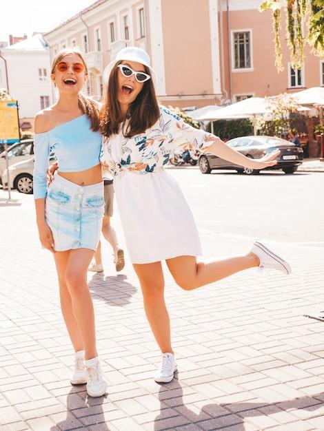 Duas jovens bonitas hipster garotas sorridentes em roupas da moda verão e chapéu panamá. Foto gratuita