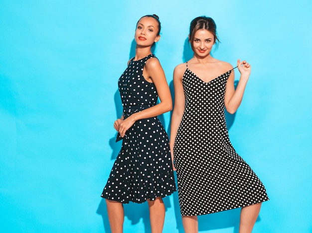 Duas jovens bonitas hipster garotas sorridentes em vestidos de bolinhas na moda verão. mulheres despreocupadas sexy posando perto da parede azul. divertindo-se e abraçando. modelos mostra bom relacionamento. fêmea com lábios vermelhos Foto gratuita