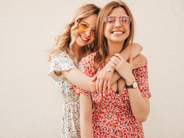 Duas jovens bonitas hipster garotas sorridentes no vestido de verão na moda. mulheres despreocupadas sexy posando na rua perto da parede em óculos de sol. modelos positivos se divertindo e enlouquecendo Foto gratuita