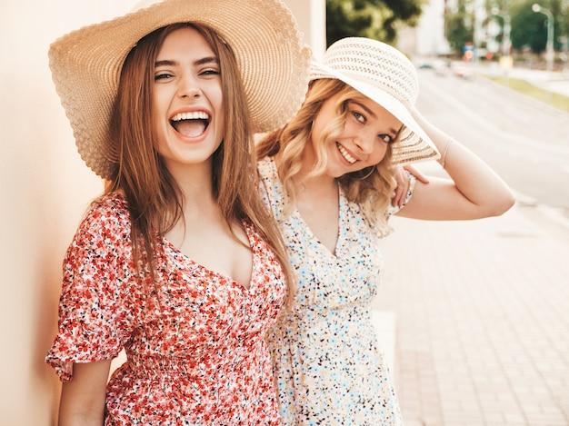 Duas jovens bonitas hipster garotas sorridentes no vestido de verão na moda. mulheres despreocupadas sexy posando no fundo da rua em chapéus. modelos positivos se divertindo e abraçando Foto gratuita