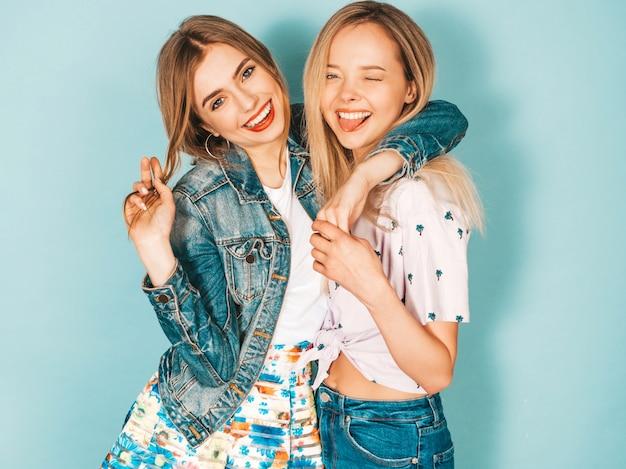Duas jovens bonitas loiras garotas hipster sorridente em roupas coloridas na moda verão. Foto gratuita