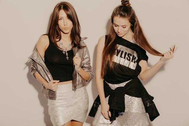Duas jovens bonitas loiras garotas hipster sorridente em roupas da moda no verão. mulheres despreocupadas sexy posando perto da parede no estúdio. modelos positivos se divertindo Foto gratuita