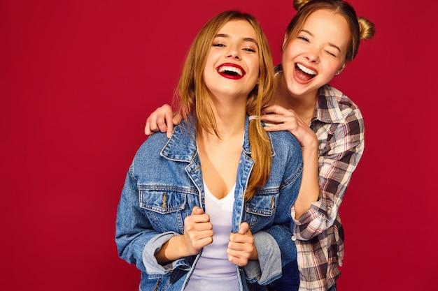 Duas jovens bonitas loiras sorrindo hipster mulheres posando em roupas de camisa quadriculada na moda verão Foto gratuita