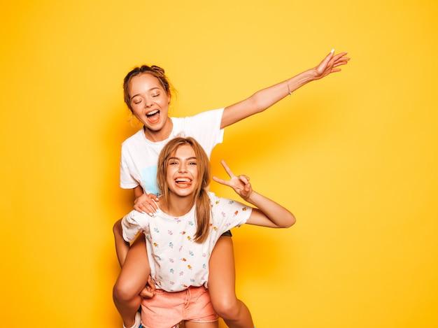 Duas jovens bonitas sorridentes garotas hipster em roupas da moda no verão. mulheres despreocupadas sexy posando perto da parede amarela. modelo sentado nas costas da amiga e levantando as mãos Foto gratuita