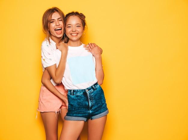 Duas jovens bonitas sorridentes garotas hipster em roupas da moda no verão. mulheres despreocupadas