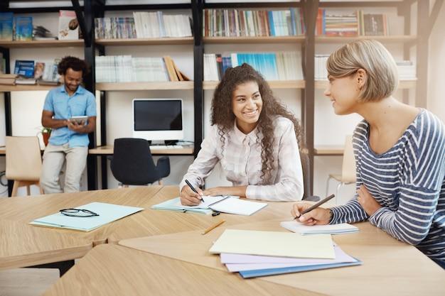 Duas jovens estudantes multiétnicas bonitas falando sobre projeto de graduação, fazendo anotações em cadernos, procurando informações em livros. Foto gratuita