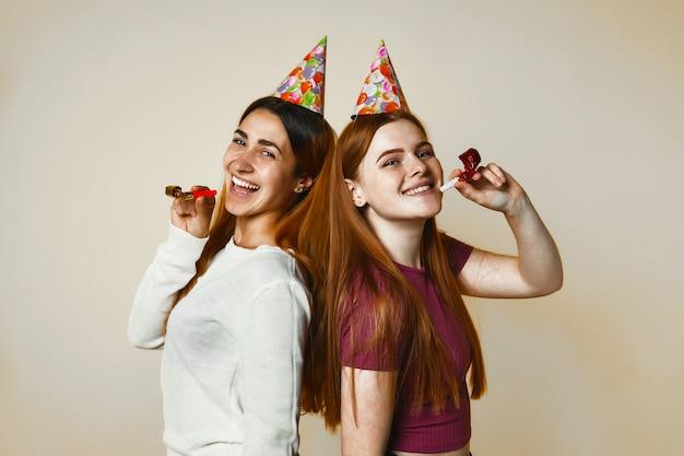 Duas jovens garotas caucasianas em chapéus de aniversário estão sinceramente sorrindo Foto gratuita