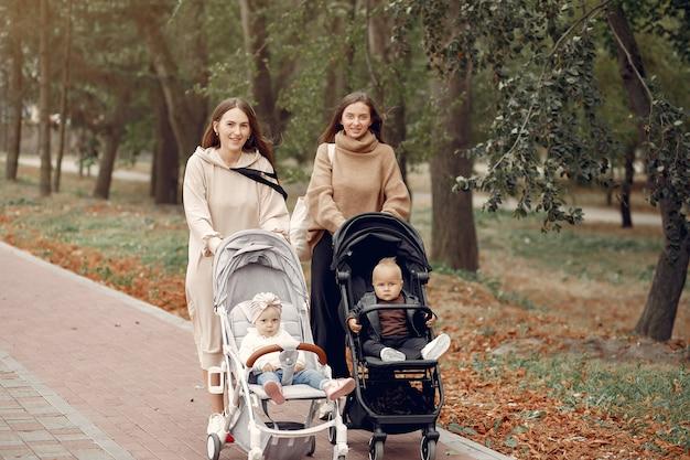 Duas jovens mães andando em um parque de outono com carruagens Foto gratuita