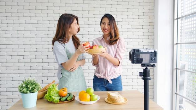 Duas jovens mulheres asiáticas blogueiros de comida falando enquanto gravava vídeo com o momento feliz Foto Premium
