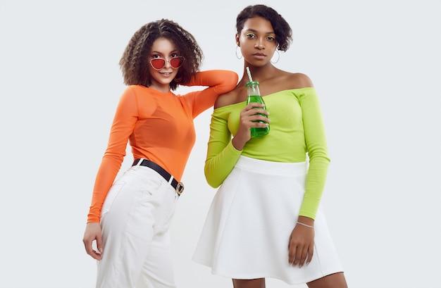Duas jovens mulheres bonitas em roupas coloridas do verão Foto Premium
