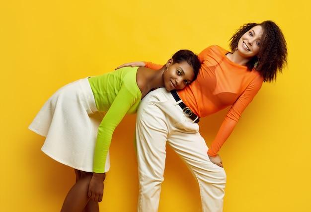 Duas jovens mulheres bonitas em roupas da moda coloridas do verão Foto Premium