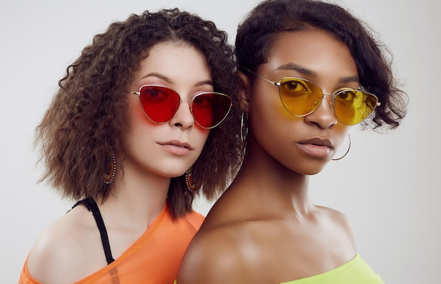 Duas jovens mulheres bonitas em roupas de verão e óculos de sol brilhantes Foto Premium