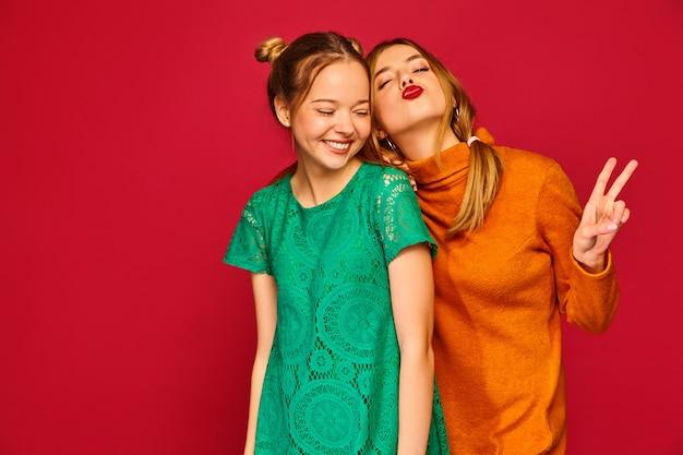 Duas jovens mulheres bonitas posando em roupas da moda Foto gratuita