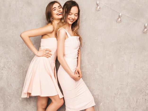 Duas jovens sorridentes lindas meninas na moda verão luz rosa vestidos. mulheres sexy despreocupadas posando. modelos positivos se divertindo Foto gratuita