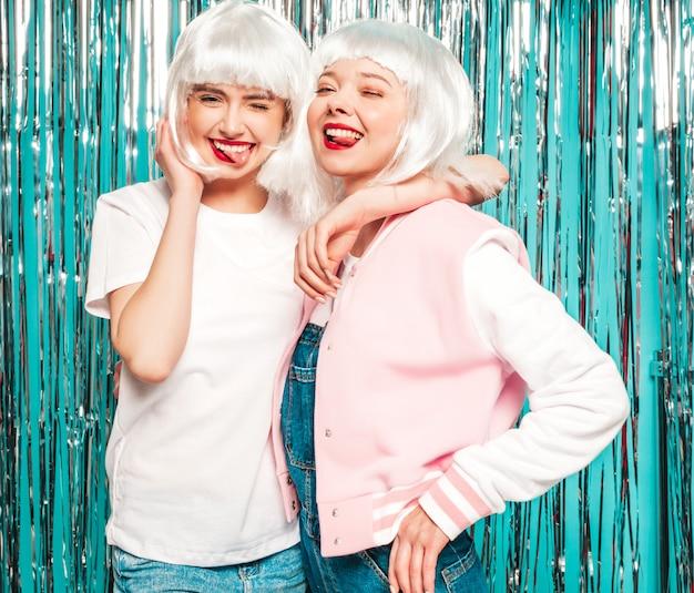 Duas jovens sorridentes sexy hipster garotas de perucas brancas e lábios vermelhos. mulheres bonitas na moda em roupas de verão. eles mostram línguas Foto gratuita