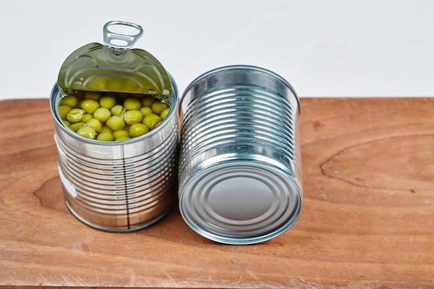 Duas latas de ervilhas cozidas em uma placa de madeira. Foto gratuita