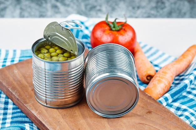 Duas latas de ervilhas cozidas, legumes e toalha de mesa sobre uma mesa de mármore e branco. Foto gratuita