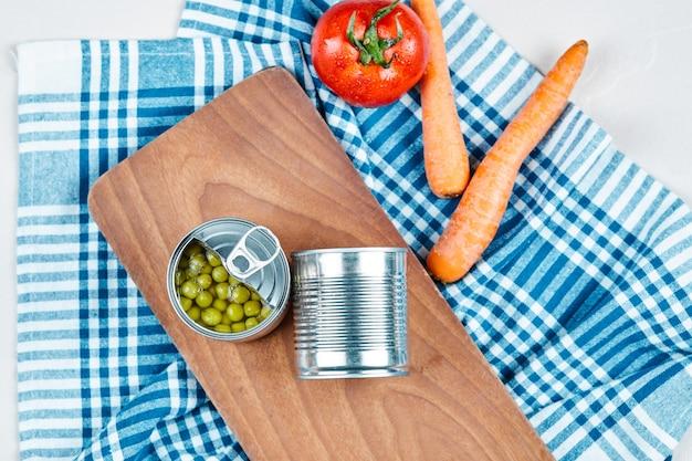 Duas latas de ervilhas cozidas, legumes e toalha de mesa. Foto gratuita