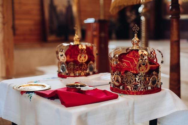 Duas lindas coroas com tecido dourado e vermelho estão sobre uma mesa na igreja antes do batismo do bebê Foto gratuita