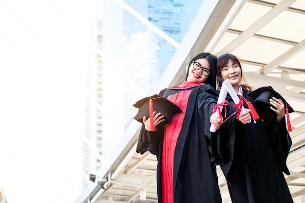Duas lindas garotas asiáticas abraçam a cerimônia de formatura Foto Premium