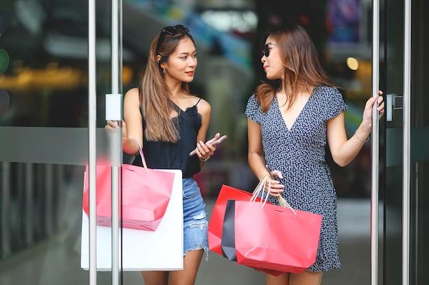 Duas lindas meninas com óculos de sol estão segurando sacolas e smartphone andando fora do shopping com felicidade. Foto Premium